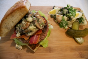 Gordon Ramsay's Herb Focaccia Burger with Sautéed Mushrooms, Blue Cheese Chive Butter, Iceberg Lettuce and Bacon, served with a Russet Potato Salad with Sour Cream, Mayo, Mustard, Olives, Dill pickles and Eggs