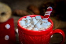 Red knitted mug filled with hot chocolate and marshmallows on wo
