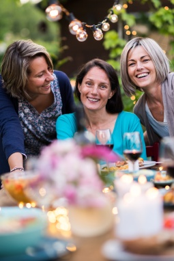 Summertime. Group of friends gathered around a table in the garden. Three beautiful women in their 40s pose for the camera.